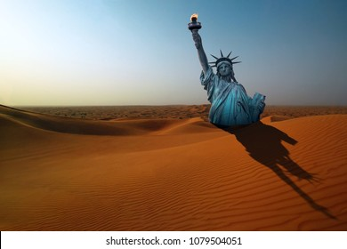 Surreal apocalyptic desert landscape with The Statue of Liberty making long shadow on the dunes