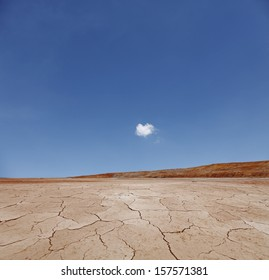 A surreal arid desert landscape with a blue cloudy sky.