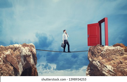 Surreal challenge overcome . Businessman conquering obstacle balancing on slack line rope above a gap  between two mountain peaks.Risk taking , success concept.