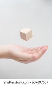 Surreal design concept - Abstract geometric real wooden cube float on girl's hand with grey background.