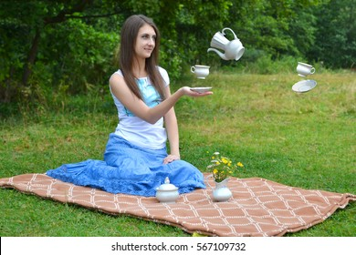 Surreal design. Young girl sitting on the grass while drinking tea. Levity white cups and teapot. Tea with an imaginary friend.