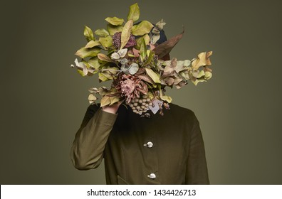 Surreal faceless portrait of woman in fashionable green clothing with dried flowers instead of face on dark green background indoors