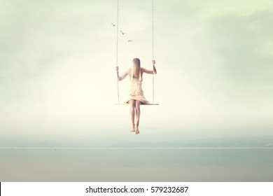 surreal fantastic woman swings on a seesaw in the air