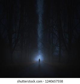Surreal horror scene with alone strange man in dark night forest. Dreamy landscape.
