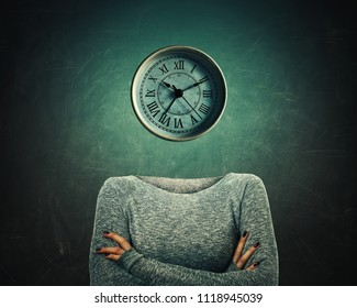 Surreal image of a confident woman with crossed hands and a clock instead of head over blackboard background. The concept of time in educational process. Business planning symbol.