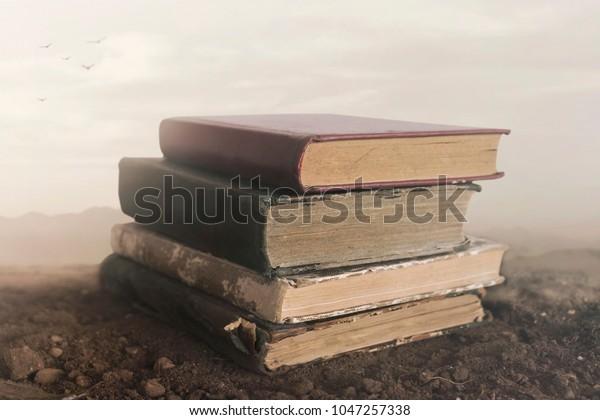 Imagen surrealista de libros gigantes uno encima del otro tocando el cielo
