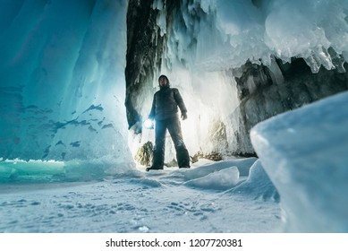 Surreal landscape with man exploring mysterious ice grotto cave. Outdoor adventure. Man exploring huge icy cave, dark majestic landscape. Magical silhouettes on background of illuminated ice blocks