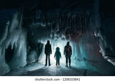 Surreal landscape with people exploring mysterious ice grotto cave. Outdoor adventure. Family exploring huge icy cave, dark majestic landscape. Magical silhouettes on background of illuminated ice