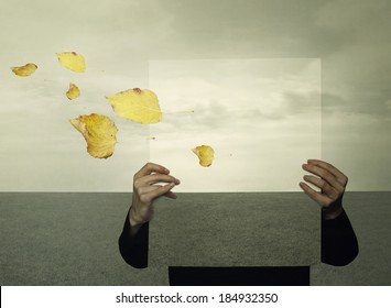 Surreal landscape with a person who holds a framework with the same landscape in the background like an optical effect and leaves in the wind