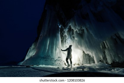 Surreal landscape with woman exploring mysterious ice grotto cave. Outdoor adventure. Girl exploring huge icy cave, dark majestic landscape. Magical silhouettes on background of illuminated ice blocks