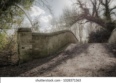 Surreal, low-contrast image of an old brick built footbridge seen in a clearing of an English forest. Detail of the weathered bricks and undulating, muddy path can be seen, crossing a small river.