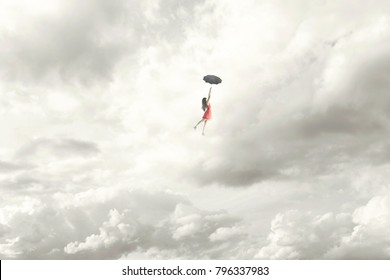 Surreal moment of an elegant woman flying in the middle of the clouds hanging on her umbrella