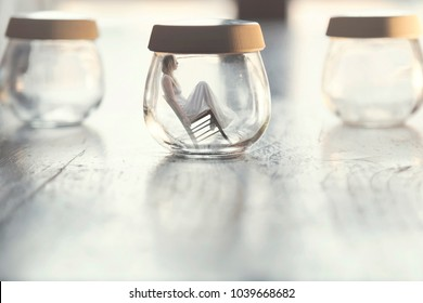 surreal moment of a tiny woman sitting on a chair inside a glass vase in the table at home