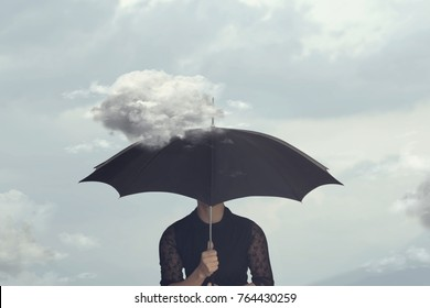 surreal moment of a woman hiding under the umbrella from a small cloud that chases her