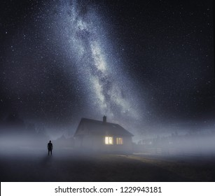Surreal night landscape with house in fog and human silhouette under starry sky. Dreamy look.