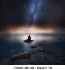 Surreal night seascape with man sitting on stone at beach under starry sky.