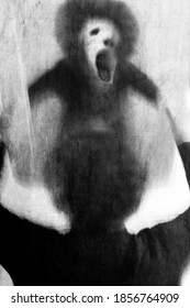 Surreal portrait of man. Horror scene with a creepy face in the mirror. Long exposure.