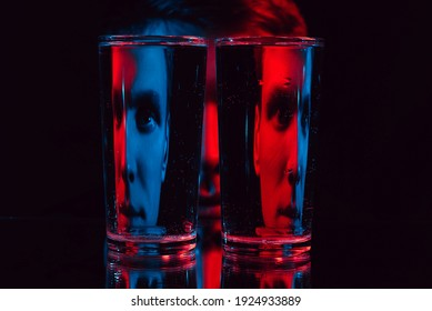 surreal portrait of a man looking through glass glasses of water with reflections and distortions with red blue neon light