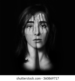 Surreal portrait of a young girl covering  her face and eyes with  her hands.Double exposure. Black and White.