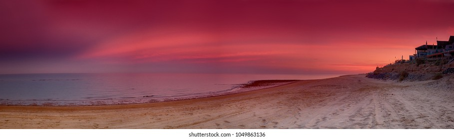 Surreal purple sunset over Sea of Cortez in San Felipe, Mexico, white sandy beach with a summer vacation house on the cliff and beautiful larger than life setting sky, super wide panorama stitch