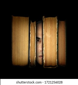 Surreal scene with close-up man's face with an amazed expression between old books on dark background. Bibliophile, education importance and imaginative literature concept