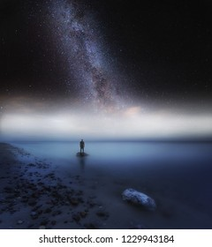 Surreal sea at night landscape with starry sky and human silhouette standing on shore. Dreamy look.