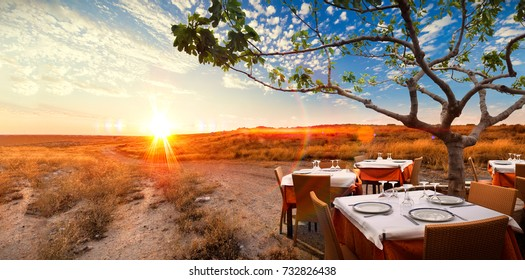 Surreal sunset landscape with table and dishes in romantic and idyllic nature.Concept of gourmet and eat in restaurant .