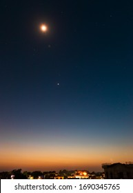 Surreal Twilight Colors. Long exposure of Lightburst Venus Planet with stars in the background and orange sky from setting sun. selective focus