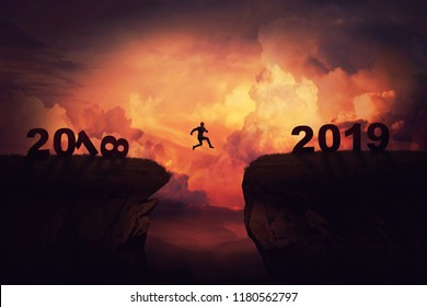 Surreal view as a businessman jump over a chasm obstacle between 2018 and 2019 years. Self overcome new year concept, way to win and success over sunset background. Achieving goals symbol.