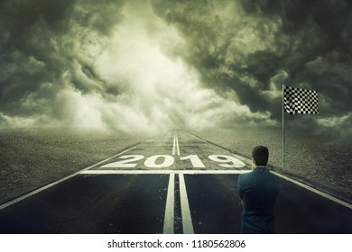 Surreal view as a competitive young businessman stand on the road in front of the start line with numbers 2019. Business challenge and motivation for a new year. Opportunity way, development concept.