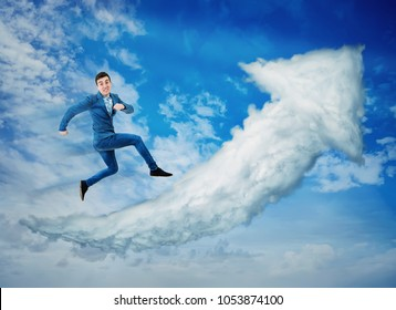 Surreal view as a happy businessman jump on a cloud graph arrow going up over a blue sky background. No limits success concept, business metaphor as keep on moving forward.