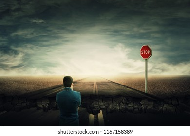 Surreal view as a man stand on a crushing asphalt road and a STOP red sign in front. Deep hole in the ground, chasm as broken way for businessman. Career difficulties and overcome for achieve success.