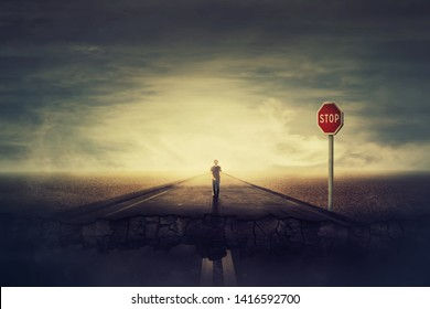 Surreal view as man walks a crushing asphalt road as STOP red sign warns of danger. Deep hole in the ground, chasm as broken way for wanderer. Career difficulties and overcome for achieve success.