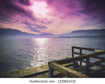Surreal view from the pier at the mountain lake with purple heaven