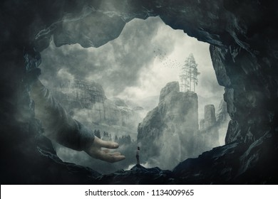 Surreal view as a wander girl silhouette on the edge of a cave stand in front of a giant stretched hand. Mystery hand of help and protection to cross the foggy chasm. Freedom concept. Unknown journey.