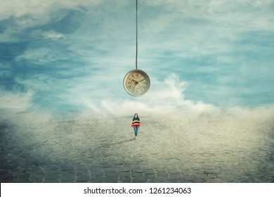 Surreal view as a woman walking on a pavement road and a suspended clock on her back hanging from the sky. The importance of time in the modern world. Time travel concept.