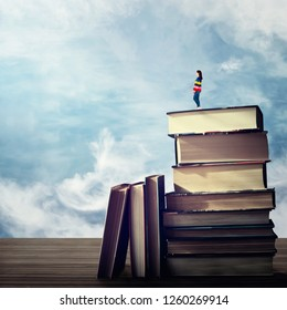 Surreal view as young woman student stand on the top of a huge pile of books looking far at horizon blue sky. Idea and knowlegde concept.