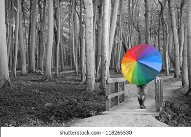 surreal - woman with colorful umbrella in the woods
