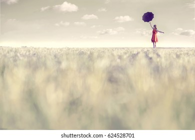 Surreal woman dressed in red walks with her umbrella in the middle of nature