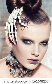 Surrealistic fashion portrait of young beautiful woman with dramatic makeup, wearing jewellery and holding a skeleton hand