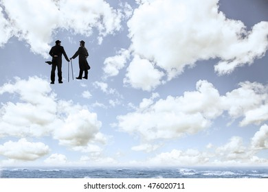Surrealistic image of silhouettes of 2 men with a cane and bowl hat chatting up in the clouds