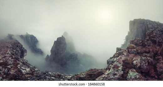 Surrealistic mountain landscape with peaks in mist