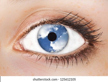 surrealistic picture of a woman's  eye with the sky in it