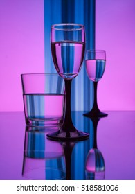 Surrealistic violet blue and pink photo still life of perfectly Transparent glasses with water. Chess effect photo. High quality Glass factory production. Crystal shining wine glasses on the mirror