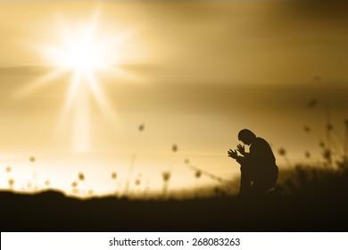 Surrender concept: Human kneel and praise God over blurred nature sunset background