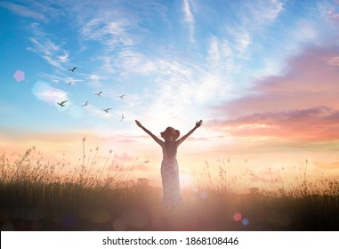 Surrender and praising concept: Silhouette of healthy Christian woman raised hands at meadow sunset background