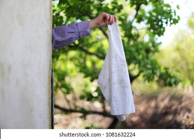Surrender,man is hiding behind a wall with a white flag, cloth as a sign of peace, negotiation or resignation on a green background, outdoors and copy space.