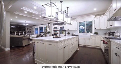 Surrey - 10. April 2020: Luxurious Dining Room And Modern Kitchen Furnished With Elegant Furniture Inside Of Spacious Interior. Style Design Concept For Dinner Table, Chair, Drawer And Chandelier.