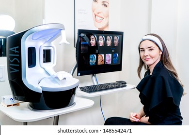Surrey, BC / Canada - 07/16/19: VISIA facial skin scanner with UV photography to show sun damage and aging, with woman looking at results.