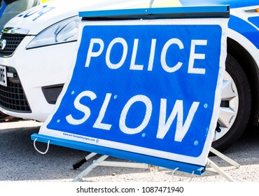 Surrey, UK. 5th May 2018. EDITORIAL - POLICE SLOW sign placed next to a patrol car which is parked by the roadside.